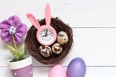 Todavía de Pascua vida Reloj rosado con los oídos de un conejo en una jerarquía y los huevos de Pascua del color Imagen de archivo libre de regalías