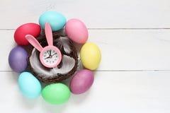 Todavía de Pascua vida Reloj rosado con los oídos de un conejo en una jerarquía y los huevos de Pascua del color Foto de archivo libre de regalías