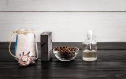 Todavía del balneario vida Aceites del aroma, piedras, jabón, sal del mar y granos de café en fondo de madera Foto de archivo libre de regalías