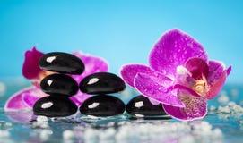 Todavía del balneario vida con la orquídea rosada y los ZENES Stone negros Imagen de archivo