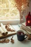 Todavía del hogar vida acogedora: palmatoria y libros en alféizar contra paisaje afuera Días de fiesta del otoño, leyendo concept Imagen de archivo