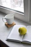 Todavía del hogar vida acogedora: taza de café caliente y de libro abierto con la manzana verde en alféizar contra paisaje de la  Fotos de archivo libres de regalías