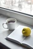 Todavía del hogar vida acogedora: taza de café caliente y de libro abierto con la manzana verde en alféizar Espacio de la copia l Imagen de archivo libre de regalías