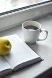 Todavía del hogar vida acogedora: taza de café caliente y de libro abierto con la manzana verde en alféizar Espacio de la copia l Imágenes de archivo libres de regalías