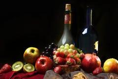 Todavía del holandés vida clásica con dos botellas de vino y de frutas mojadas en un fondo oscuro, horizontales Imagen de archivo