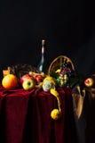 Todavía del holandés vida clásica con la botella polvorienta de vino y de fruta en un fondo oscuro Imagenes de archivo
