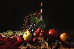 Todavía del holandés vida clásica con la botella polvorienta de vino y de frutas en un fondo oscuro Imágenes de archivo libres de regalías
