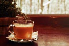 Todavía del invierno vida acogedora: taza de cacao caliente con vapor, en alféizar de madera contra paisaje de la nieve del exter Fotografía de archivo libre de regalías