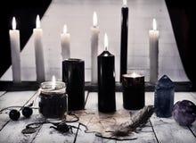 Todavía del místico vida con las velas negras y pentagram en el papel Imagenes de archivo