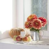 Todavía del otoño la vida con las dalias rojas en un tarro de la lata, calabaza, una taza de té y manzanas en la ventana en tiemp Fotos de archivo