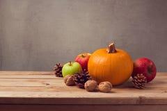 Todavía del otoño vida con la calabaza, las manzanas y el maíz del pino en cubierta de madera Foto de archivo libre de regalías