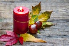 Todavía del otoño vida con la vela en viejos tableros Foto de archivo libre de regalías