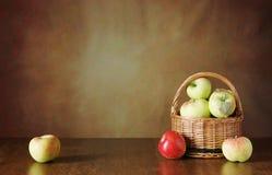 Todavía del otoño vida con las manzanas frescas en una cesta de mimbre Foto de archivo libre de regalías