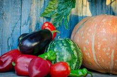 Todavía del otoño vida de verduras Berenjena, calabaza, pimientas, sandía en el viejo fondo Fotos de archivo