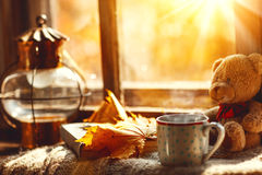 Todavía del otoño vida Una ventana, libro de taza caliente del té Fotografía de archivo