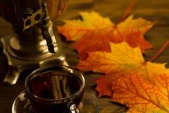 Todavía del té vida con el samovar, hojas de arce, en fondo de madera Fotos de archivo libres de regalías