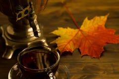 Todavía del té vida con el samovar, hojas de arce, en fondo de madera Vacie abierto un libro del vintage Foto de archivo libre de regalías