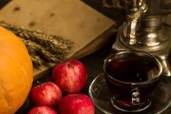 Todavía del té vida con el samovar, manzanas, calabazas anaranjadas maduras, hojas de arce, trigo en fondo de madera Imagen de archivo libre de regalías