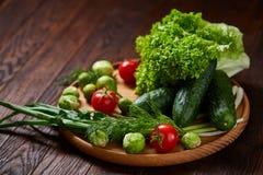 Todavía del vegetariano vida de verduras frescas en la placa de madera sobre el fondo rústico, primer, endecha plana Fotos de archivo libres de regalías