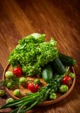 Todavía del vegetariano vida de verduras frescas en la placa de madera sobre el fondo rústico, primer, endecha plana Foto de archivo libre de regalías