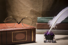 Todavía del vintage vida con los vidrios en el libro viejo cerca del inkstand y la pluma en fondo de la lona Imágenes de archivo libres de regalías