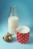Todavía del vintage vida con rojo, en lunar, la taza de leche, huevos de codornices, y la botella de cristal del vintage Fotografía de archivo libre de regalías