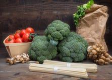Todavía el bróculi de la col de las verduras de la vida con los tomates prolifera rápidamente fondo de madera de las hojas del ve Imagen de archivo libre de regalías