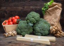 Todavía el bróculi de la col de las verduras de la vida con los tomates prolifera rápidamente fondo de madera de las hojas del ve Imágenes de archivo libres de regalías