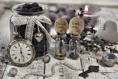 Todavía entonada la vida con las botellas minúsculas con las etiquetas me come y bebe me, los relojes viejos, llave y la baya de  Imagen de archivo