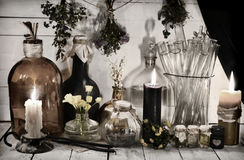 Todavía entonada vida con las botellas y tarros alquímicos, velas ardientes e hierbas curativas Fotos de archivo libres de regalías