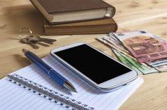 Todavía foto de la vida del smartphone, cuaderno, libro, lápiz, dinero Imagen de archivo libre de regalías