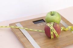 Todavía fotografía de la vida con dos manzanas, mesaure de la cinta y una escala Foto de archivo