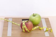 Todavía fotografía de la vida con dos manzanas, mesaure de la cinta y una escala Fotos de archivo