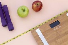 Todavía fotografía de la vida con las manzanas, cinta métrica del peso y una escala Imágenes de archivo libres de regalías