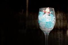 Todavía fotografía de la vida con Santa Claus en un vidrio de vino con hielo en noche con el fondo oscuro, Imágenes de archivo libres de regalías