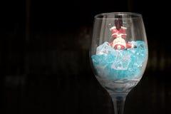 Todavía fotografía de la vida con Santa Claus en un vidrio de vino con hielo en noche con el fondo oscuro, Foto de archivo libre de regalías