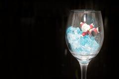 Todavía fotografía de la vida con Santa Claus en un vidrio de vino con hielo en noche con el fondo oscuro, Imagen de archivo