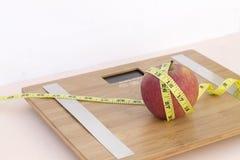 Todavía fotografía de la vida con una manzana, mesaure de la cinta y una escala Imagen de archivo libre de regalías