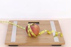 Todavía fotografía de la vida con una manzana, mesaure de la cinta y una escala Imágenes de archivo libres de regalías
