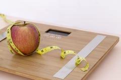 Todavía fotografía de la vida con una manzana, mesaure de la cinta y una escala Fotografía de archivo libre de regalías