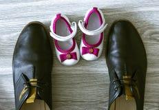 Todavía fotografía de la vida: zapatos del padre y de la hija en el piso de madera Imagenes de archivo