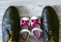 Todavía fotografía de la vida: zapatos del padre y de la hija en el piso de madera Fotos de archivo
