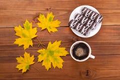 Todavía galletas del café de la vida y hojas de otoño en una tabla de madera Foto de archivo