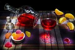 Todavía jarra de la vida y un vidrio de los bocados caramelo y naranja del vino rojo Imágenes de archivo libres de regalías