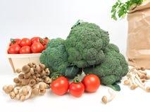 Todavía la col de las verduras de la vida que el bróculi con los tomates prolifera rápidamente las hojas verdes aisló el fondo bl Foto de archivo
