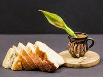 Todavía la composición de la vida con la tabla de cortar de madera de la cocina, el pan y el pote de cerámica con Arum florecen Imagen de archivo