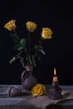Todavía la vida con amarillo marchitó las flores y la palmatoria con la oficina Foto de archivo libre de regalías