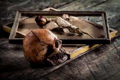 Todavía la vida con el cráneo y las rosas humanos se secó en un marco Imagen de archivo