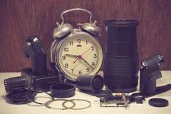 Todavía la vida con el despertador roto viejo, lente de cámara rota, vino Imagen de archivo libre de regalías