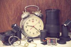 Todavía la vida con el despertador roto viejo, lente de cámara rota, vino Fotos de archivo libres de regalías